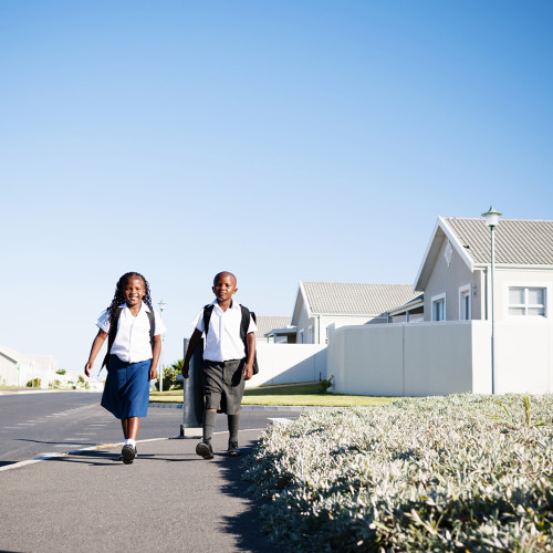 Smiling young brother & sister in school uniform walking on the sidewalk to school